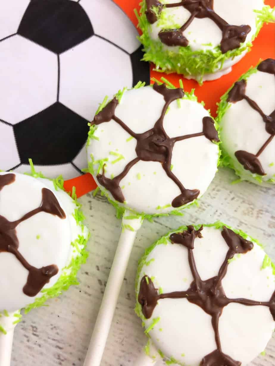These DIY Soccer cookies are super easy to make. Add a lollipop stick to each one so they are portable and less-mess after a soccer game! via @SidelineWarrior